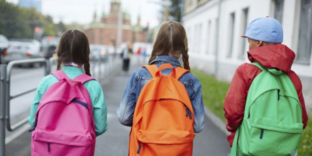 Backs of schoolkids with colorful rucksacks moving in the