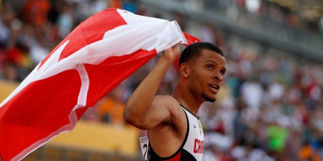 TORONTO, ON - JULY 24: Andre De Grasse of Canada holds the Canadian flag after winning the men's 200...