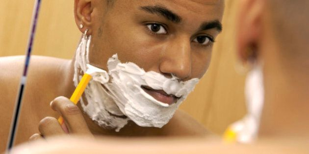 An over the shoulder headshot of an African-American young adult male's reflection in a mirror, he is shaving