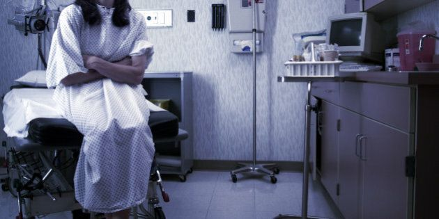 a caucasian female patient in a hospital gown sits in an exam room and waits