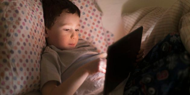 USA, New Jersey, Jersey City, Boy (6-7) using digital tablet in