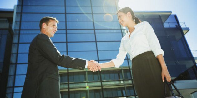 Businessman and businesswoman shaking hands below
