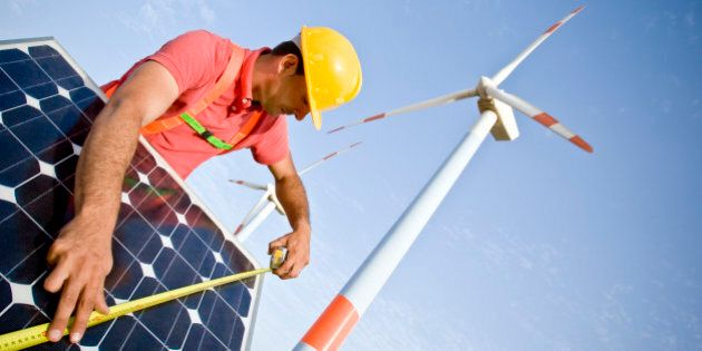 Image of a worker measuring a solar panel. In the background you can see Wind Turbines. Two different...
