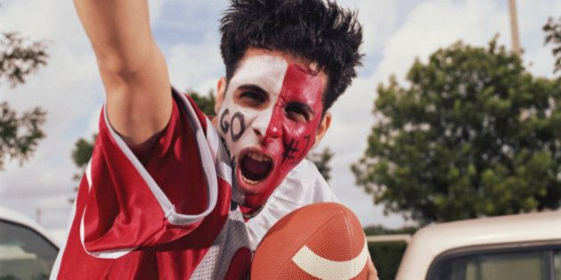 Young man with painted face, cheering and holding