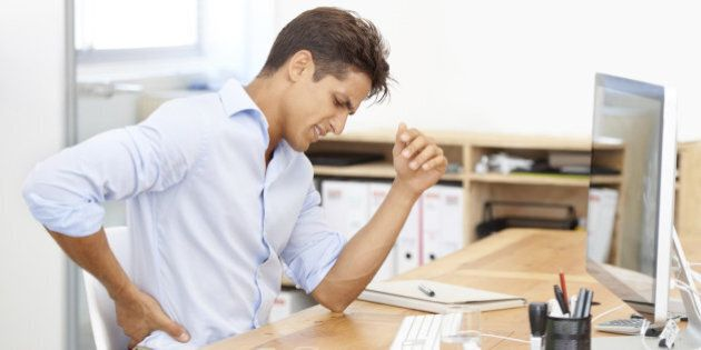 Shot of a businessman rubbing his aching back while sitting at his desk in front of his