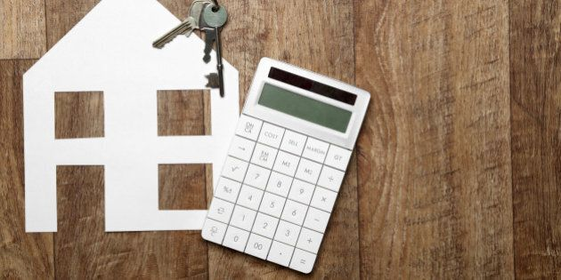 Cutout paper house on a wooden background with keys and calculator