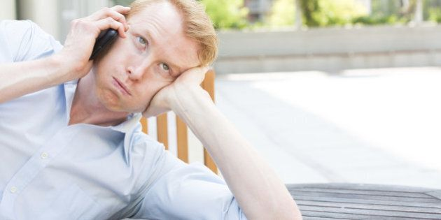Closeup portrait, worried young man in blue shirt talking on phone to someone, looking up, isolated outdoors...
