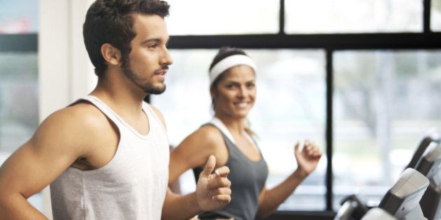 Cheerful smiling and beautiful people running at the fitness club.