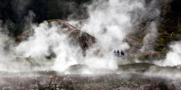 Visitors watch as steam rises from the ground at the Craters of the Moon Geothermal Park near Taupo,...