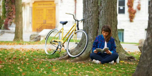 Girl reading book on university campus in fall with yellow bicycle; Kingston, Ontario,