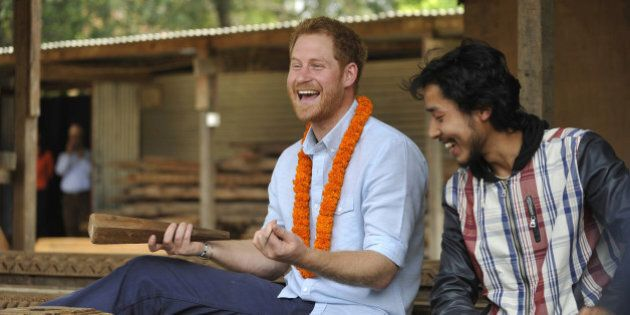 Britain's Prince Harry laughs as he tries wood carving in heritage sites at Patan Durbar Square on the...