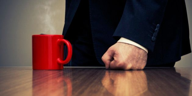 Close-up of Businessman Hitting Desk with Fist Beside Coffee