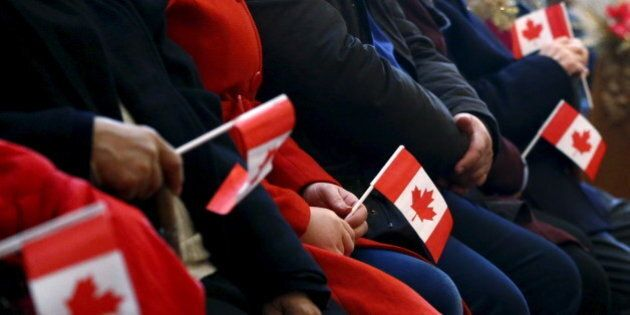 Syrian refugees hold Canadian flags as they take part in a welcome service at the St. Mary Armenian Apostolic...