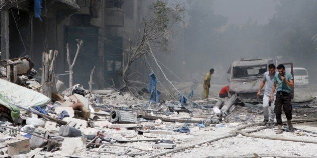 ALEPPO, SYRIA - AUGUST 27: Syrian people try to rescue people from the wreckage of collapsed buildings...