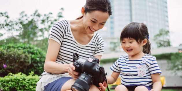 Pretty young mom showing pictures to lovely little girl from the back of the camera on the stone steps in the park in front of commercial buildings, while both smiling joyfully.