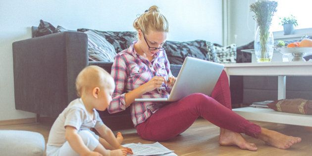 Attractive blonde woman working on a laptop computer while her barefoot baby plays around. The woman is casually dressed with long blonde hair that is swept back from her face. She looks concentrated and she is probably doing her budget or paying bills. Also, she could be a business woman that works at home. The shot is executed with available natural light, and the copy space has been left. Shallow DOF. Soft focused.