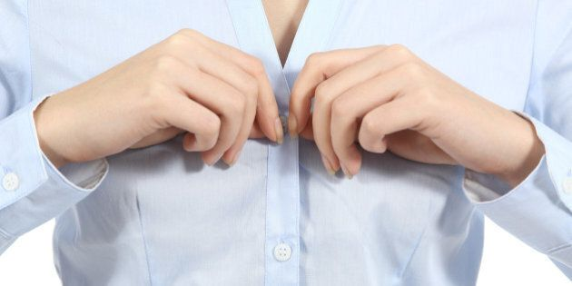 Closeup of a woman hands unbuttoning a shirt isolated on a white