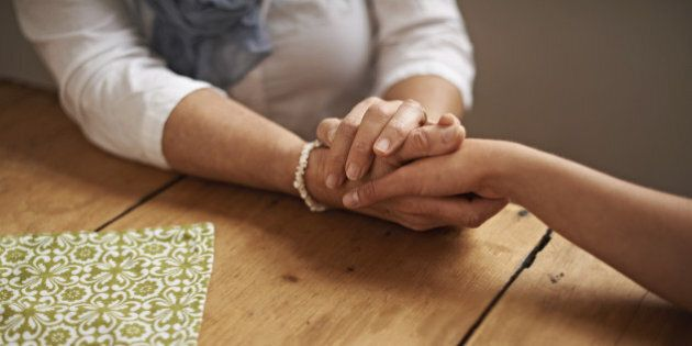 A cropped shot of a woman holding a loved one's hand in