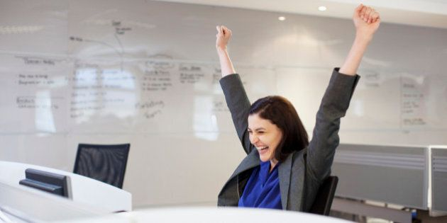 Enthusiastic businesswoman with arms raised in