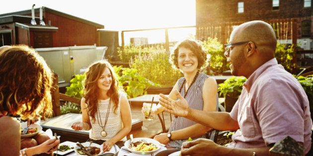 Laughing group of friends sitting together sharing dinner and wine in rooftop garden on summer