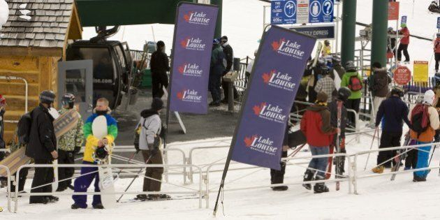 LAKE LOUISE, ALBERTA, CANADA - 2010: Skiers prepare to jump on a chair lift at Lake Louise Mountain Resort...