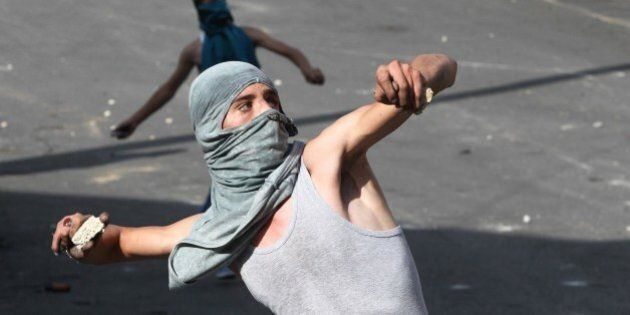 Palestinian youths throw stones towards Israeli security forces during clashes in the West Bank town...