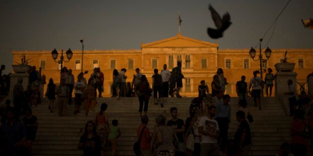 People walk in front of the Greek Parliament in central Athens, Tuesday, July 14, 2015. The eurozone's top official says it's not easy to find a way to get Greece a short-term cash infusion that will help it meet upcoming debt repayments. (AP Photo/Emilio Morenatti)