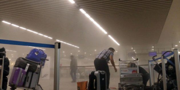 In this photo provided by Ralph Usbeck an unidentified traveller gets to his feet in a smoke filled terminal...