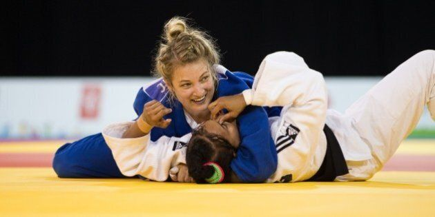 Kelita Zupancic (Top) of Canada smiles as she pins Onix Cortes of Cuba to win the gold medal in the women's...