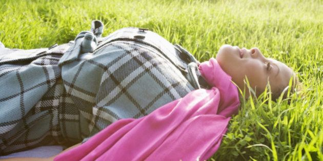 Profile of fashionable, multi ethnic woman lying in the grass on a sunny day.
