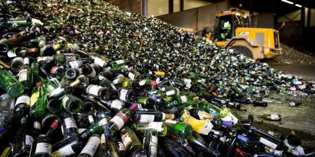 A bulldozer of a glass recycling processing plant makes a mountain of bottles in Gameren, following the...