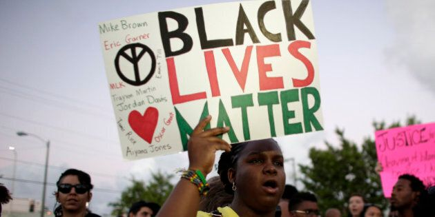 Desiree Griffiths, 31, of Miami, holds up a sign