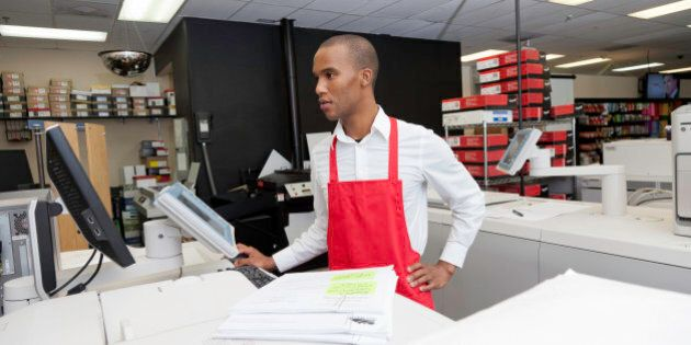 Manual worker looking at cash register
