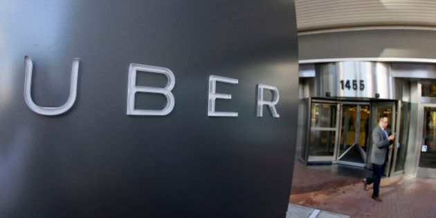 FILE - In this photo taken Tuesday, Dec. 16, 2014, a man leaves the headquarters of Uber in San Francisco....