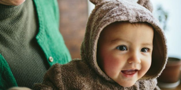 Cheerful mixed race baby girl wearing a bear costume.
