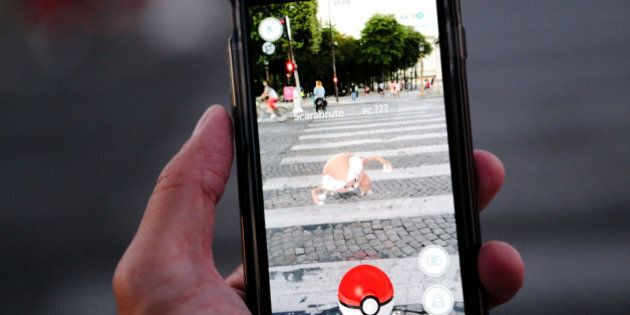 PARIS, FRANCE - AUGUST 17: A man launches a Pokeball to catch a Scarabrute (Pinsir) character while playing...