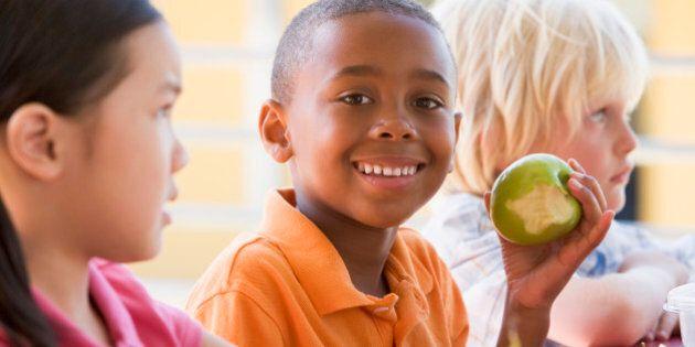 Kindergarten children eating lunch smiling at