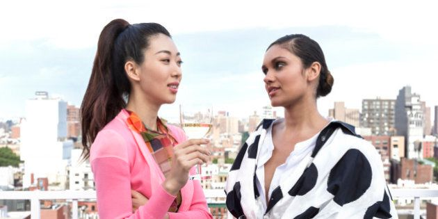 two beautiful stylish young woman of diverse ethnicities having a drink, glass of wine  on city rooftop with view of city behind them