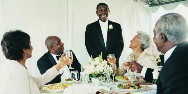 Young Man Standing to Give a Speech at a Wedding Reception