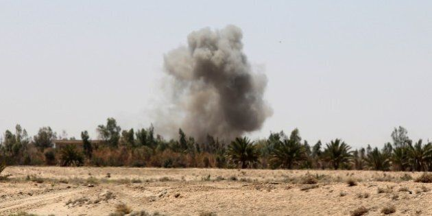 Smoke rises from a village on the outskirts of the city of Fallujah, west of the capital Baghdad, during...