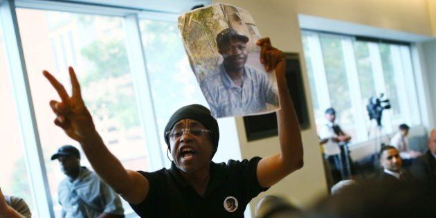 TORONTO, ON - SEPTEMBER 1: Cecil Peter holds up a photo of Andrew Loku, who last month was shot by police...