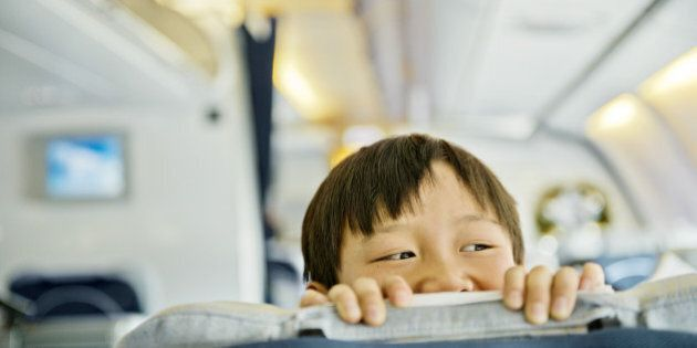 Boy looking over business class seat of