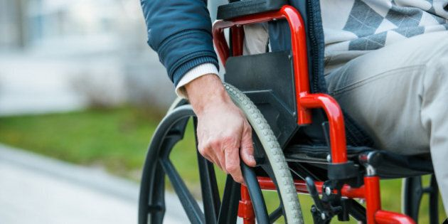 Adult man in wheelchair. Close up photo of male hand on wheel of wheelchair during