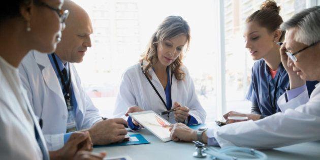 Doctors using digital tablet in
