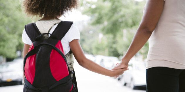 african american mom and daughter hold hands while