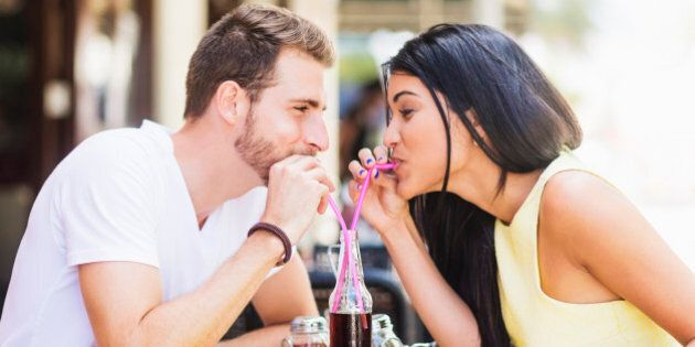 Hispanic couple drinking soda at