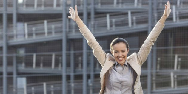 Excited young businesswoman with arms raised standing against office