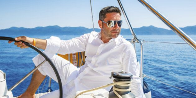 Handsome man sailing with sailboat.