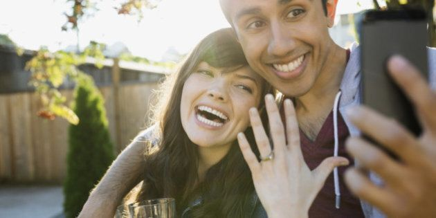 Enthusiastic couple taking selfie of engagement ring