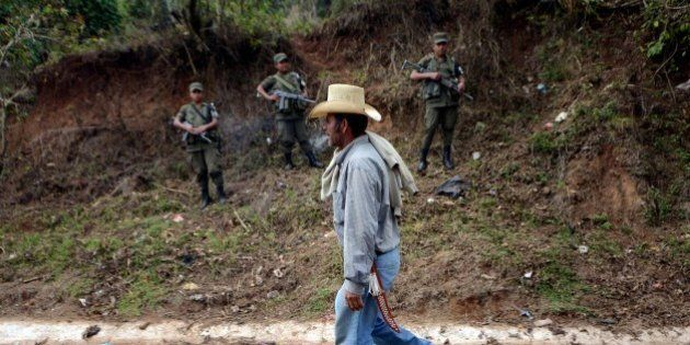 An man walks along a road as soldiers stand guard in Mataquescuintla municipality, Jalapa departament,...